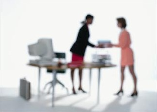 Blurred image of a woman standing at a desk receiving items from another woman.