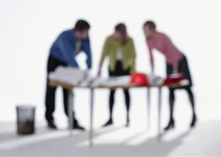 Blurred image of three people leaning over a table.