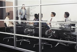 Image through a window of several adults in business attire in a classroom.