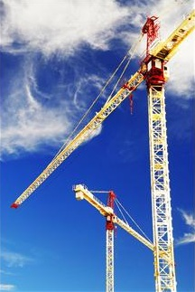 Photograph of two cranes against a blue sky.